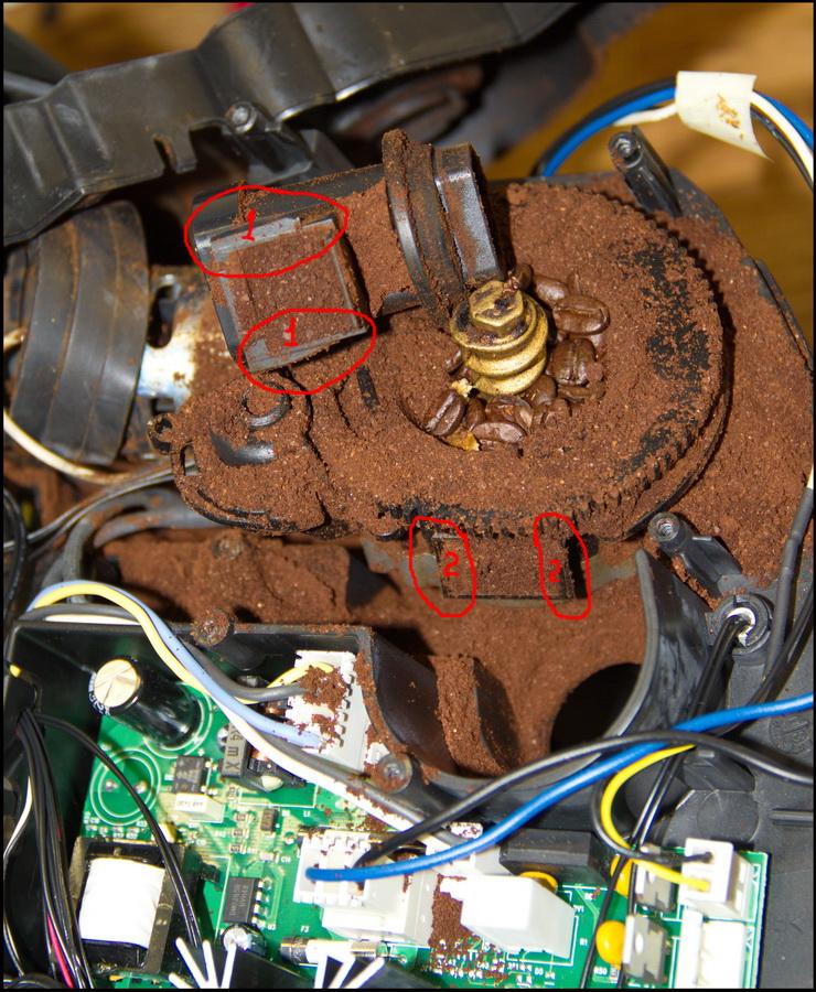Сломанные ушки кофемолки (1), перестали надёжно крепиться к корпусу кофемолки (2). Итог на фото.
